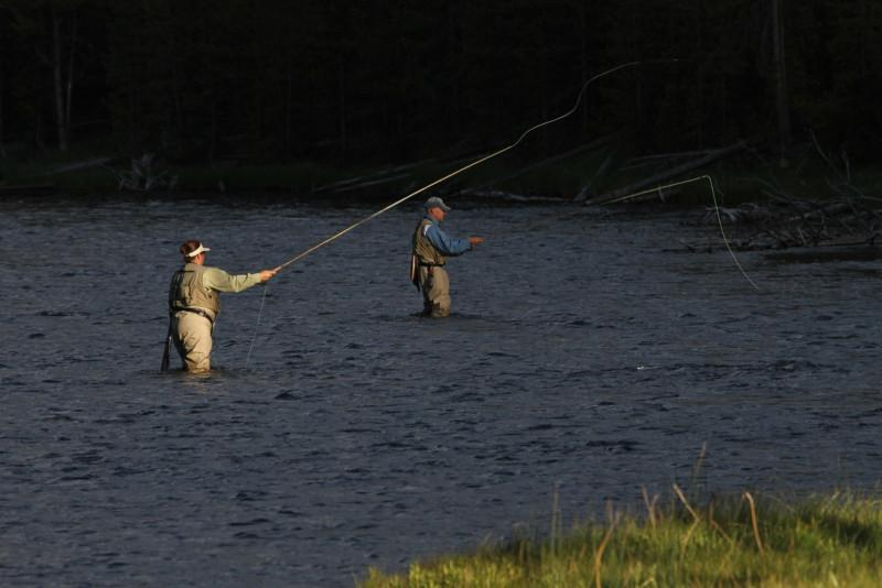 A man and woman fly fish beside one another