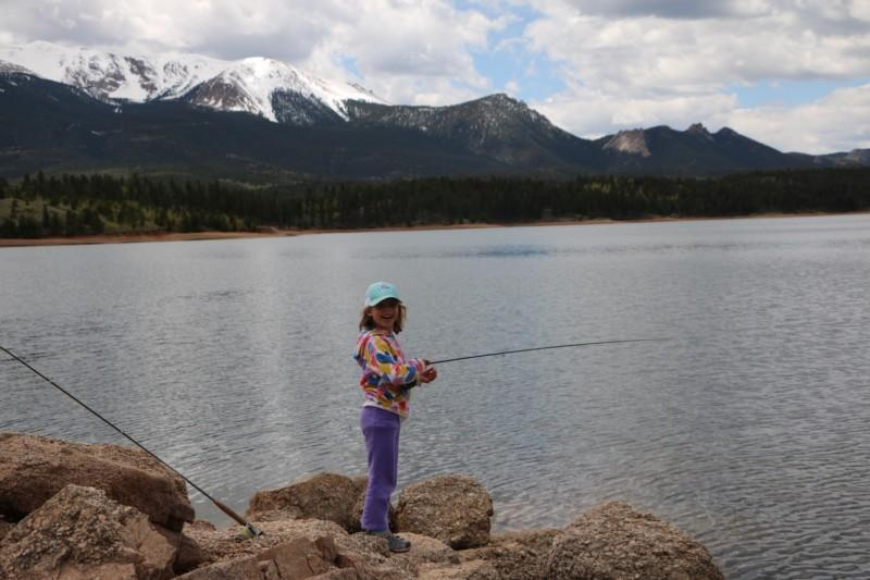 An angler smiles for the camera while fishing the scenic North Slope Lakes