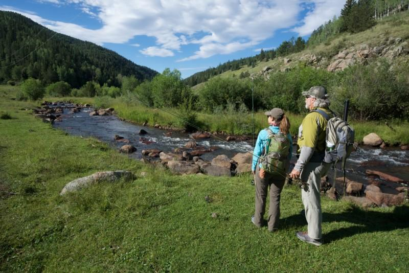 A man and woman hike next to a babbling mountain brook