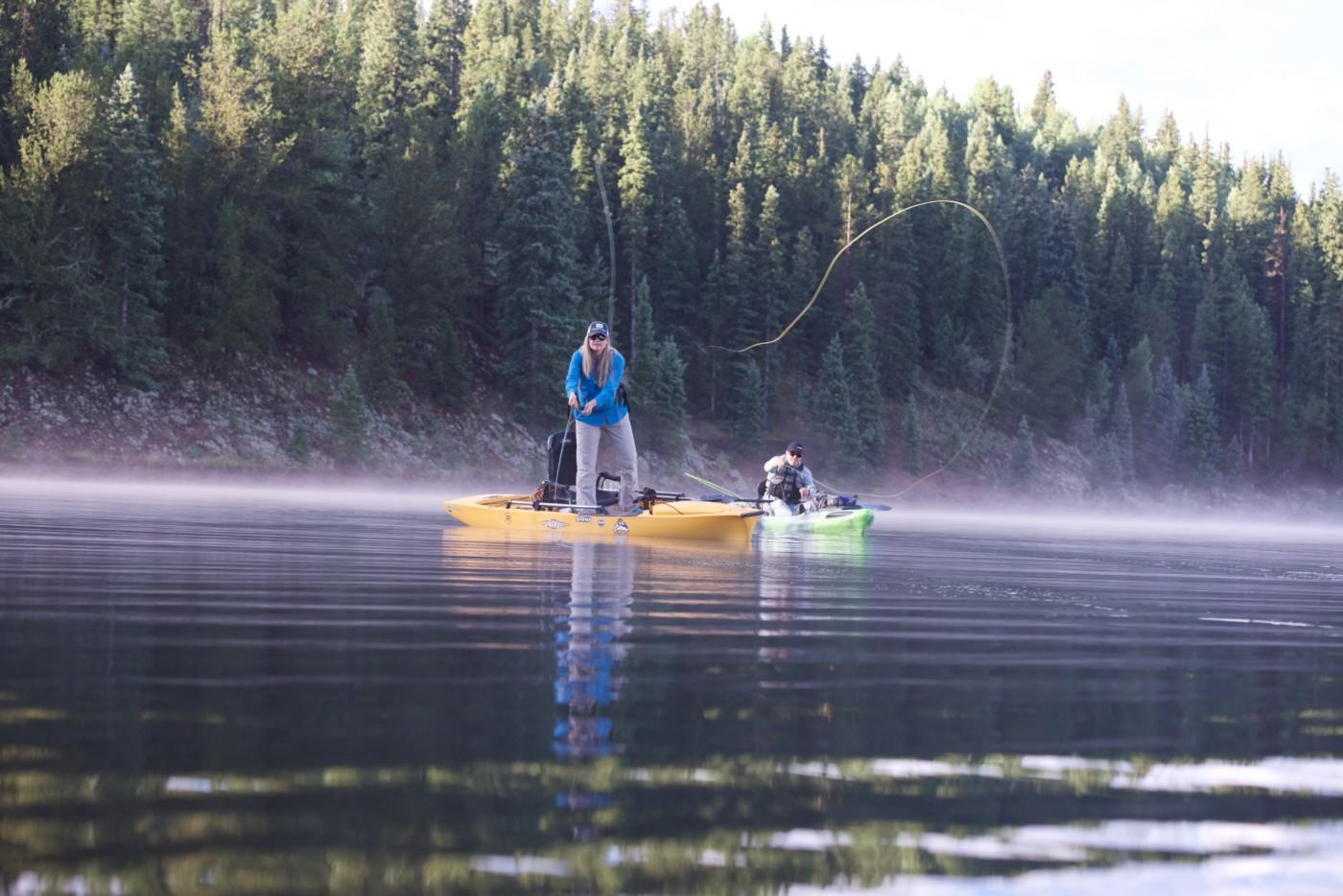 Angler on kayak casts into a misty mountain lake
