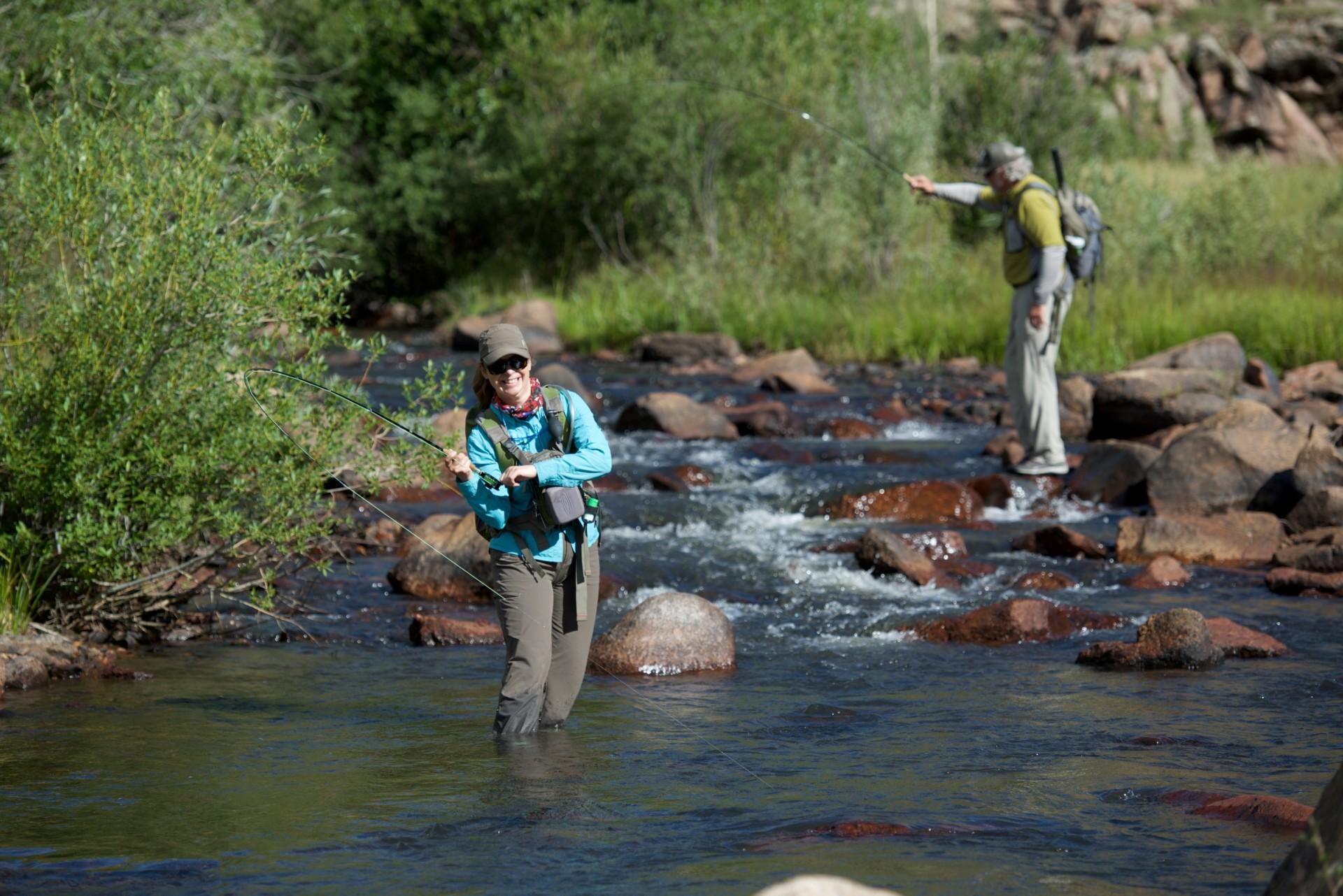 A man and woman fly fishing in picturesque Colorado mountain stream