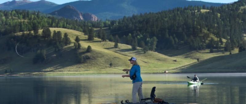 Man and woman float fly fishing on a mountain lake.