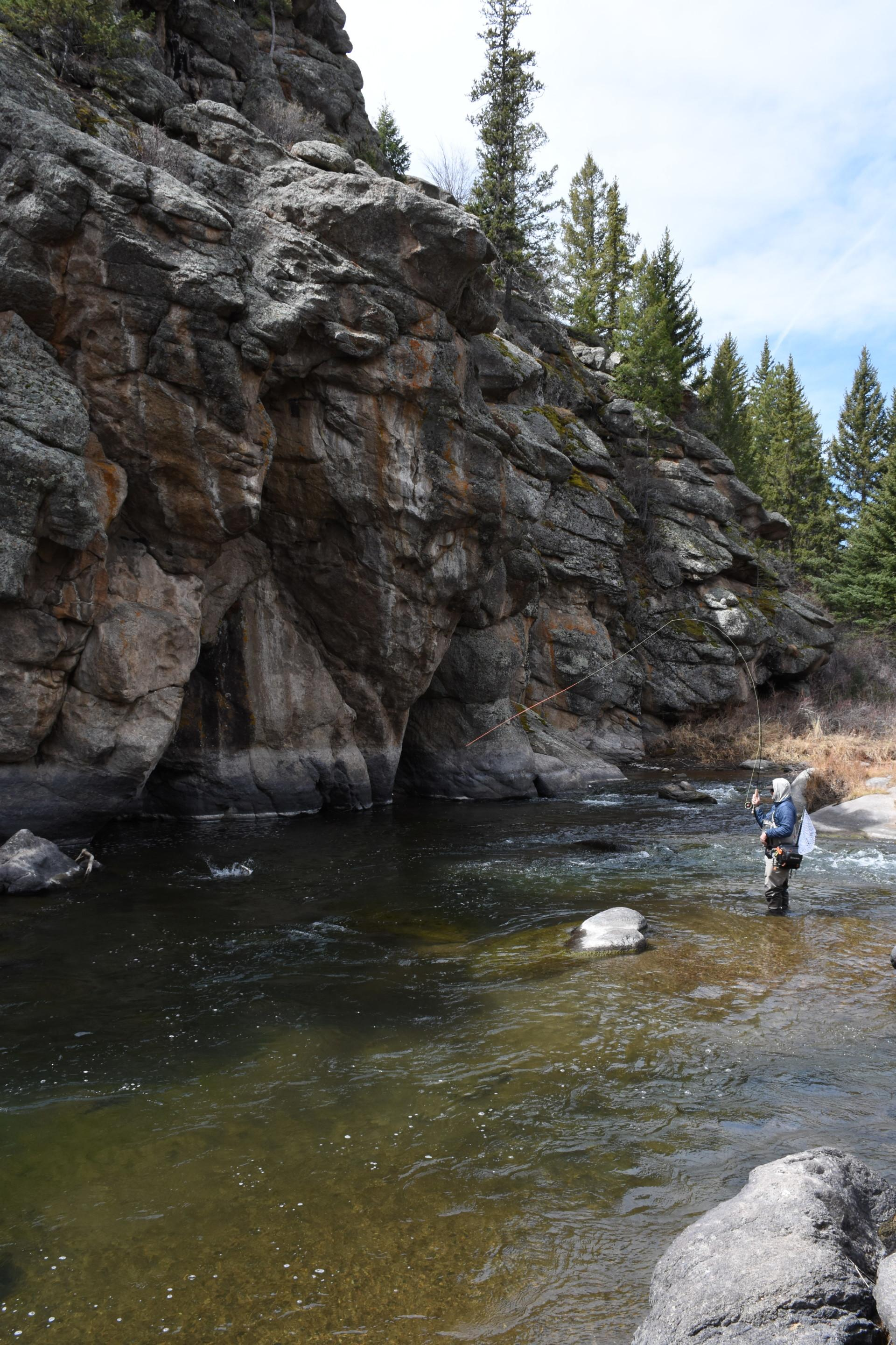 Angler fly fishing near rock wall