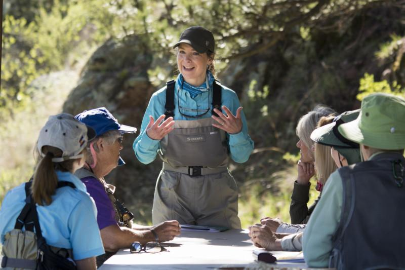 A guide shares her wisdom with other fisherwomen around a table