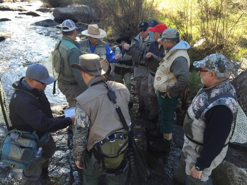 A small group of students and guides listens streamside